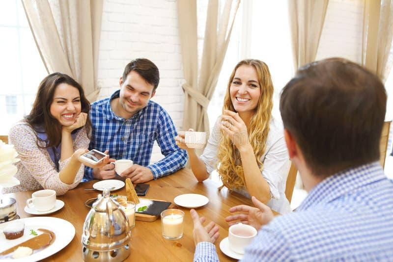 Grupo de quatro amigos felizes que encontram e que falam e que comem o desse imagem de stock
