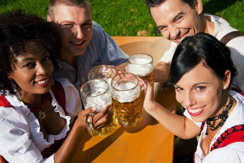 Grupo de quatro amigos no jardim da cerveja foto de stock