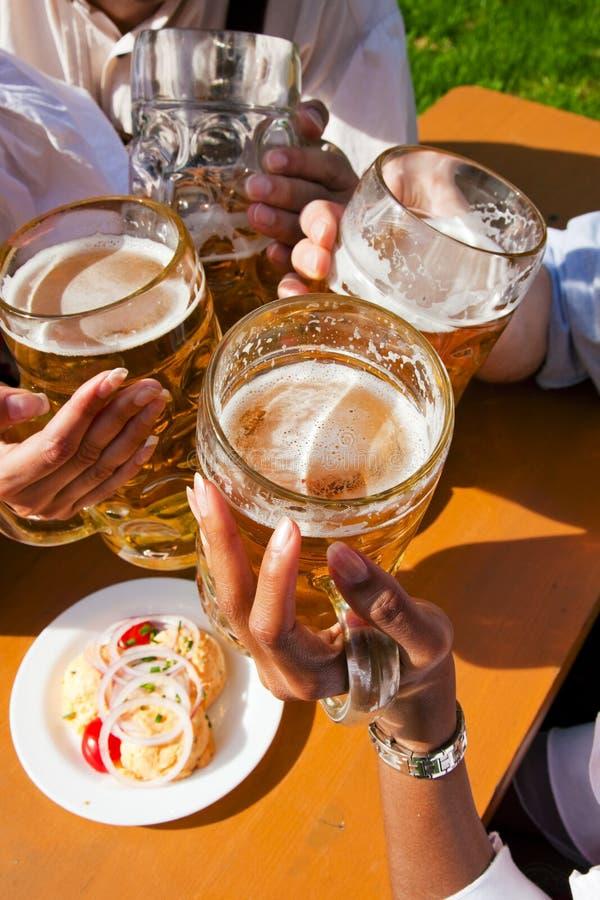 Grupo de quatro amigos que bebem a cerveja imagens de stock royalty free