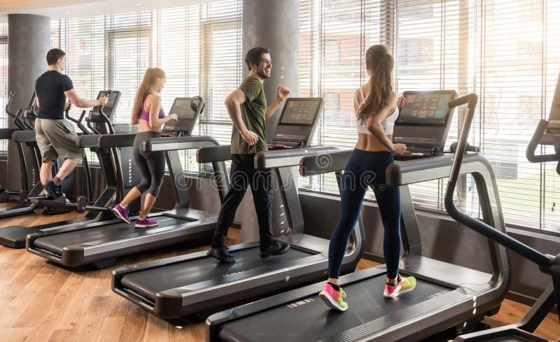 Grupo de quatro povos que correm em escadas rolantes no gym da aptidão imagem de stock