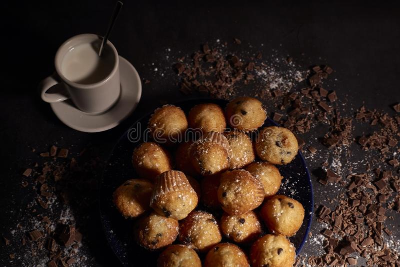 Grupo de queques ao lado de um copo do leite imagens de stock royalty free