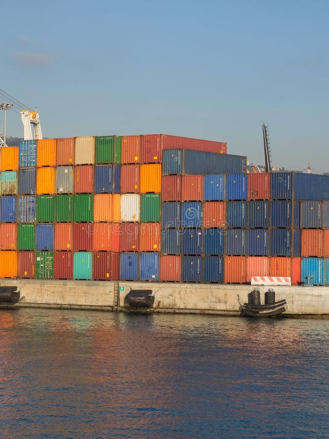Grupo de recipientes coloridos no porto que reflete na água foto de stock royalty free