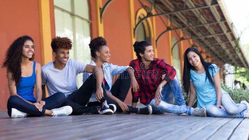 Grupo de relaxamento de adultos novos do multi moderno étnico imagens de stock royalty free