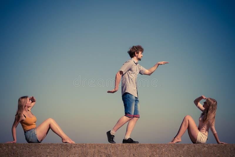 Grupo de relaxamento das meninas do menino dois dos amigos exterior imagem de stock royalty free