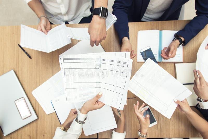 Grupo de reuni?n de negocios en la tabla en la oficina moderna, el trabajo del equipo y las manos diversas juntas uni?ndose a las fotos de archivo libres de regalías