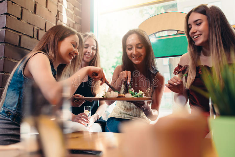 Grupo de rir as jovens mulheres bonitas que compartilham do alimento que senta-se na cafetaria fotos de stock