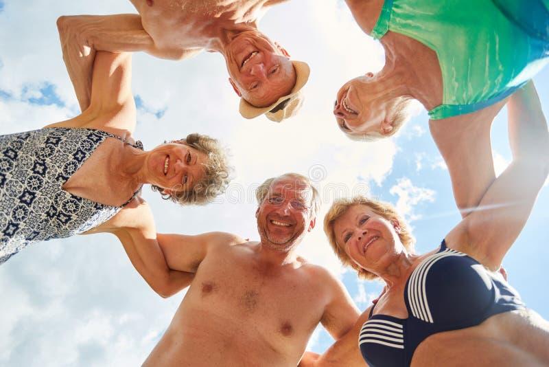 Grupo de riso de sêniores no círculo no verão fotos de stock royalty free