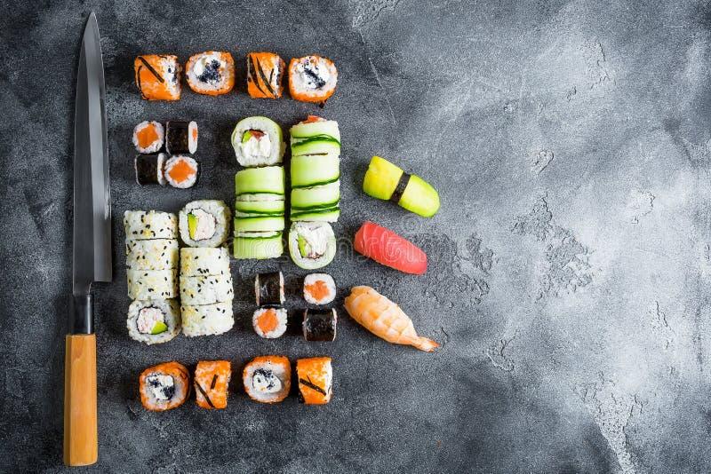 Grupo de rolos e de faca de sushi no fundo escuro Alimento japonês tradicional Copie o espaço Configuração lisa Vista superior foto de stock royalty free