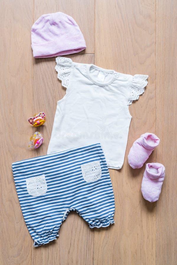 grupo de roupa e de artigos para a criança em um fundo de madeira dos t-shirt, das calças, das peúgas e das chupetas imagens de stock royalty free
