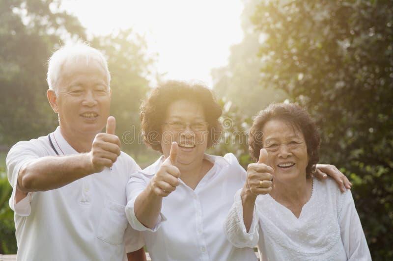 Grupo de sêniores asiáticos que dão os polegares acima imagens de stock royalty free