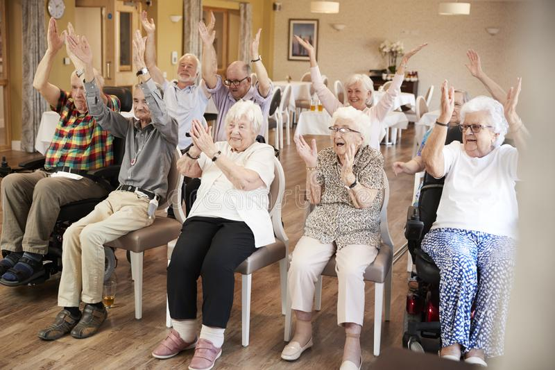 Grupo de sêniores que apreciam a classe da aptidão no lar de idosos imagens de stock