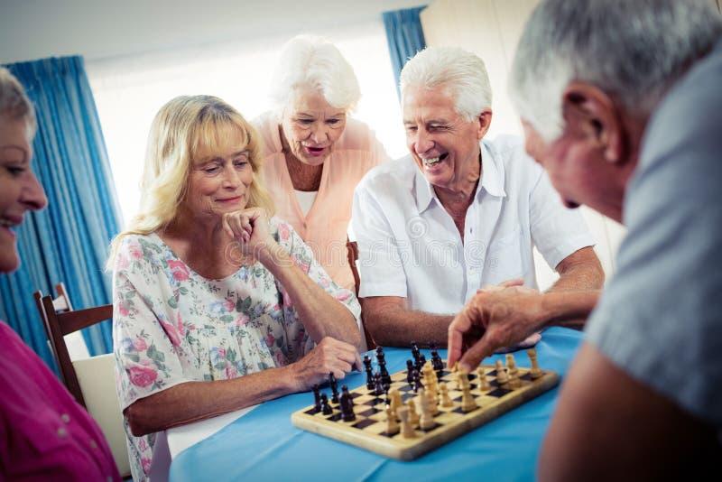 Grupo de sêniores que jogam a xadrez fotos de stock