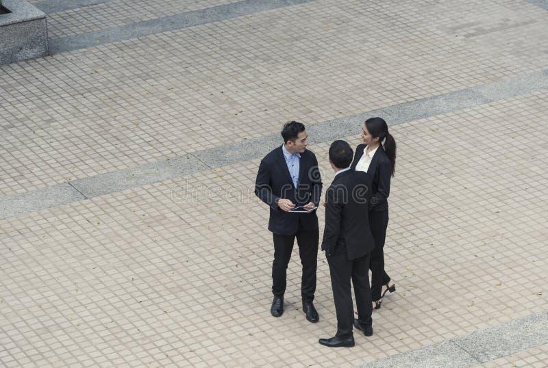 Grupo de sócio asiático do negócio que discute ao andar no prédio de escritórios conceito social do colega fotos de stock royalty free