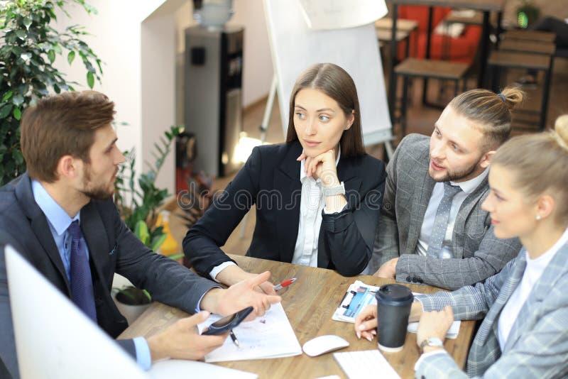 Grupo de s?cios comerciais que discutem estrat?gias na reuni?o no escrit?rio imagem de stock