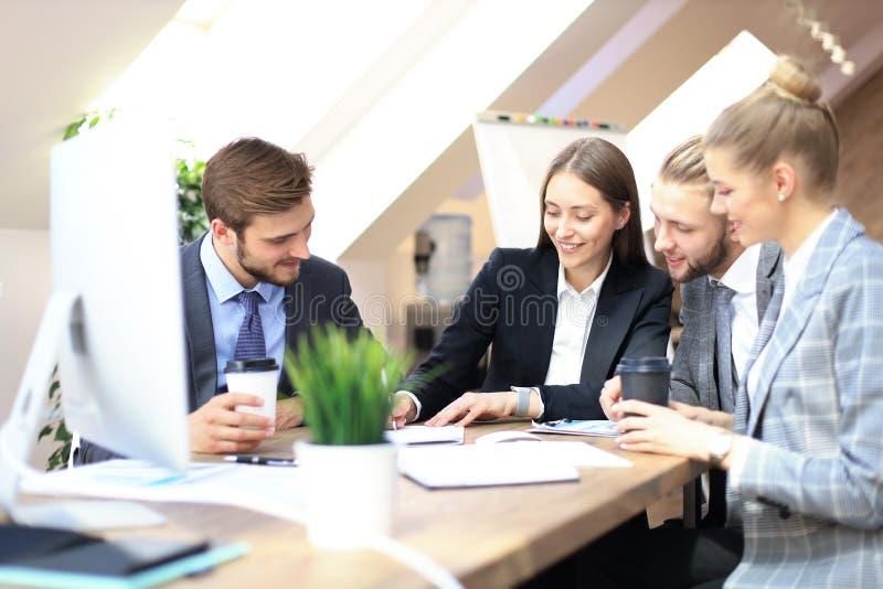 Grupo de s?cios comerciais que discutem estrat?gias na reuni?o no escrit?rio fotografia de stock royalty free
