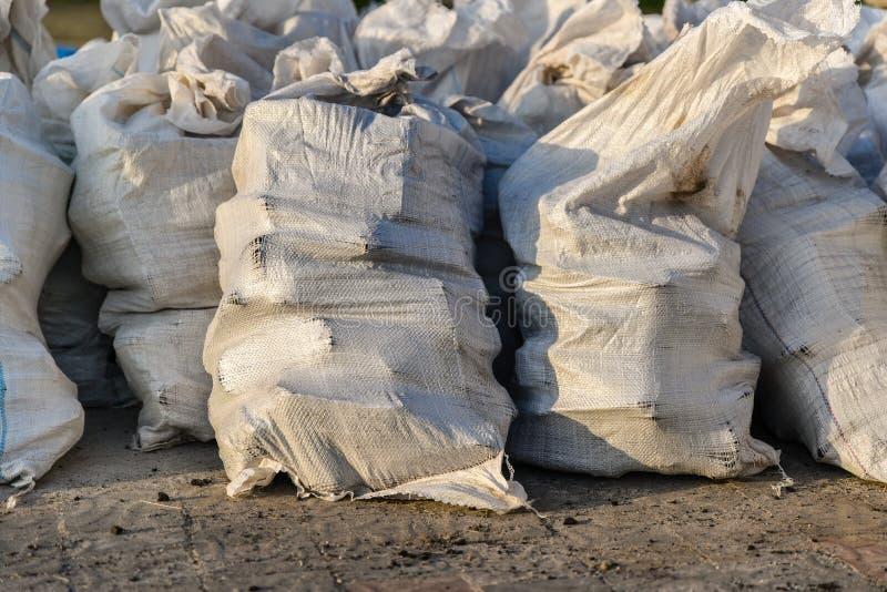 Grupo de sacos tecidos pl?sticos enchidos, embalagem dos bens para o transporte e armazenamento em um armaz?m, sacos do polipropi fotos de stock royalty free