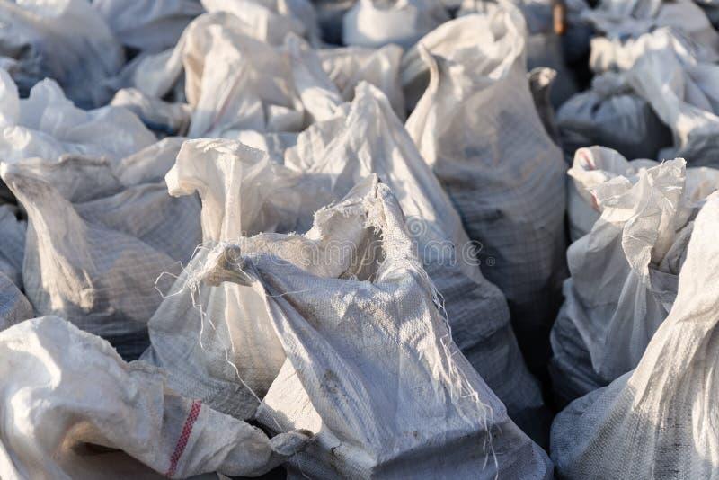 Grupo de sacos tejidos plásticos llenados, el embalar de las mercancías para el transporte y almacenamiento en un almacén, bolsos fotos de archivo