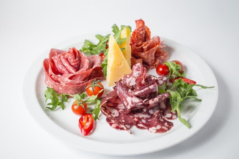 Grupo de salsichas italianas com verde, tomates, pimentão e rúcula imagem de stock