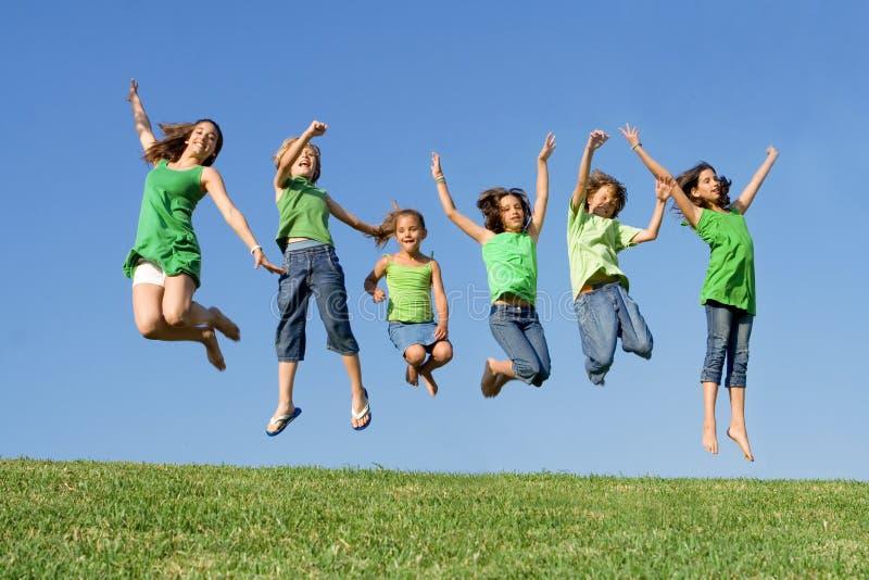 Grupo de salto feliz dos miúdos foto de stock royalty free
