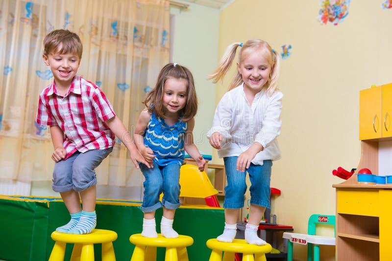Grupo de salto preescolar feliz de los niños imagenes de archivo