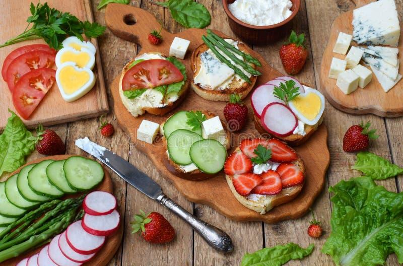 Grupo de sanduíches inteiros saudáveis do pão integral com fuits, vegetais, queijo e as ervas verdes frondosas na tabela de madei imagem de stock royalty free