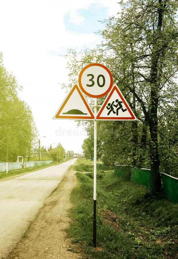 Grupo de señales de tráfico con límite de velocidad, corriendo alrededor de niños, una sección peligrosa de un camino del pueblo fotografía de archivo