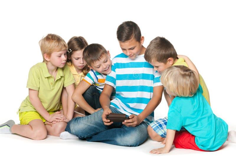 Grupo de seis crianças com um dispositivo novo imagem de stock royalty free