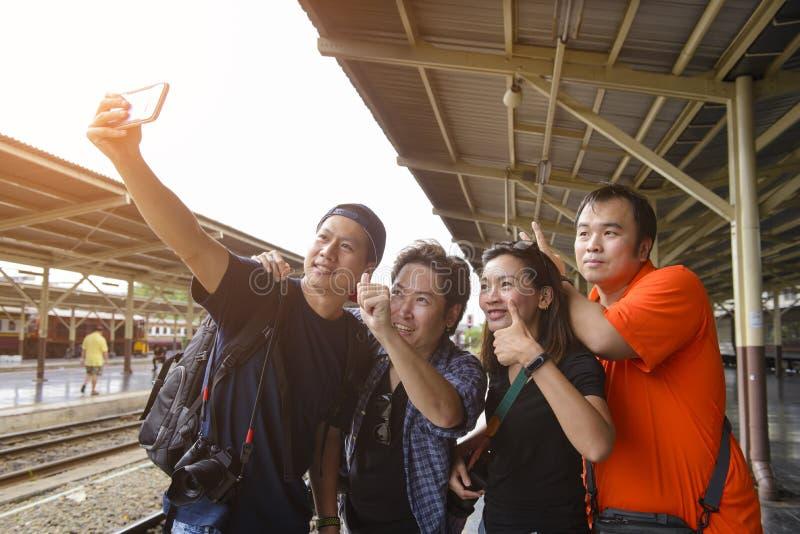 Grupo de selfie de quatro amigos com um telefone esperto em um estação de caminhos-de-ferro no verão imagem de stock royalty free