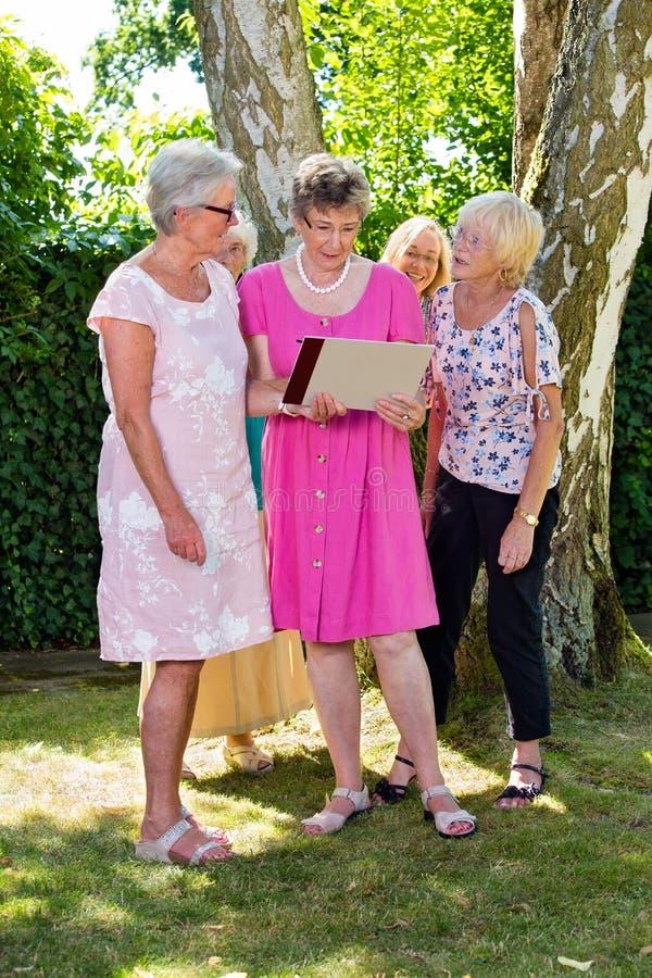 Grupo de senhoras superiores felizes que olham realizar da mulher da imagem uma em suas mãos, estando fora no parque no verão foto de stock