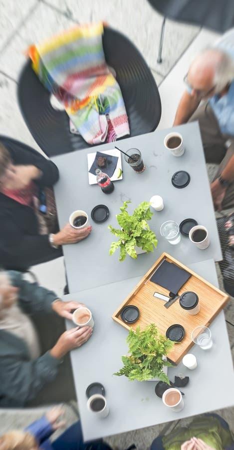 Grupo de sete pessoas adultas que encontram-se no café da manhã exterior, sobre imagens de stock royalty free