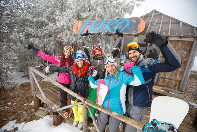 Grupo de snowboarders en casa de madera del invierno fotografía de archivo libre de regalías