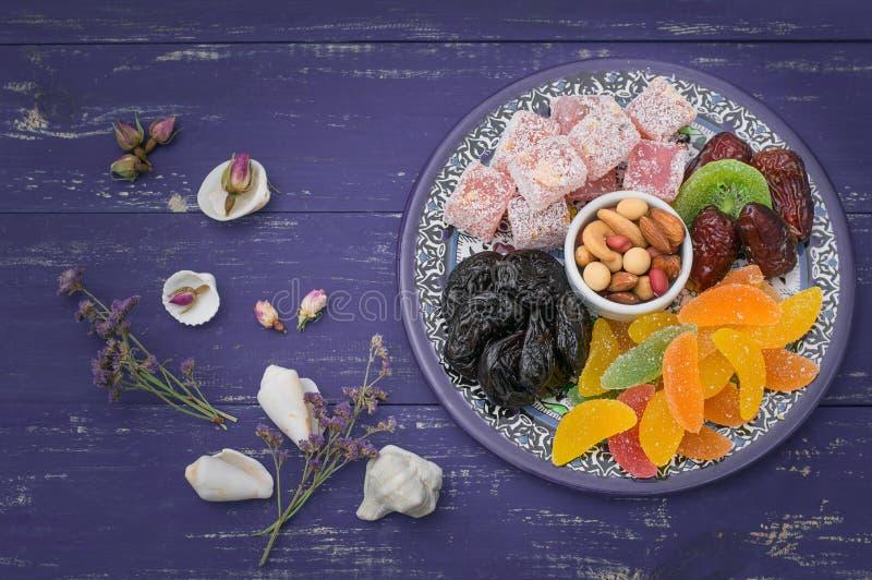 Grupo de sobremesas orientais Doce de fruta, kivi, ameixas secas, lokum do rahat, porcas, o mandarino, caqui, abricós secados, pi foto de stock