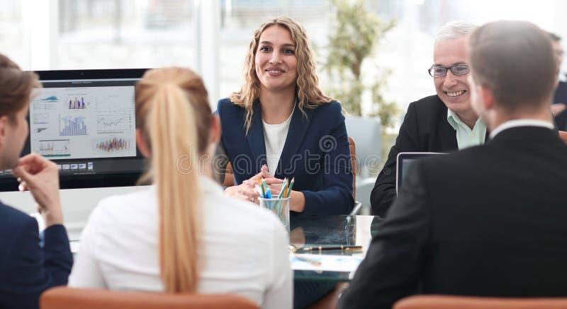 Grupo de socios comerciales confiados que discuten el papel en la reunión foto de archivo
