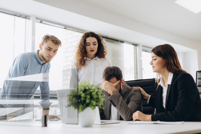 Grupo de socios comerciales jovenes que trabajan en oficina moderna Compañeros de trabajo que tienen problema mientras que trabaj imagen de archivo