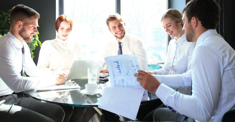 Grupo de socios comerciales que discuten ideas y que planean el trabajo en oficina fotos de archivo