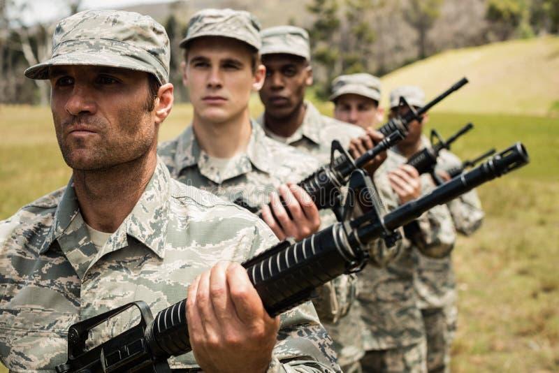 Grupo de soldados militares que estão com rifles fotos de stock royalty free