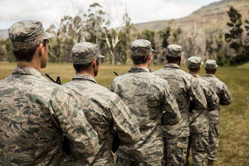 Grupo de soldados militares que estão com rifles fotos de stock
