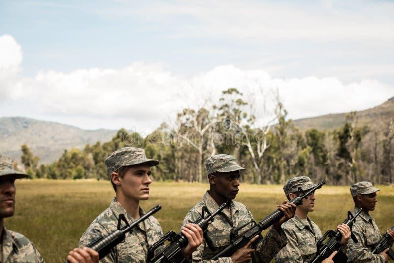 Grupo de soldados militares que se colocan con los rifles foto de archivo
