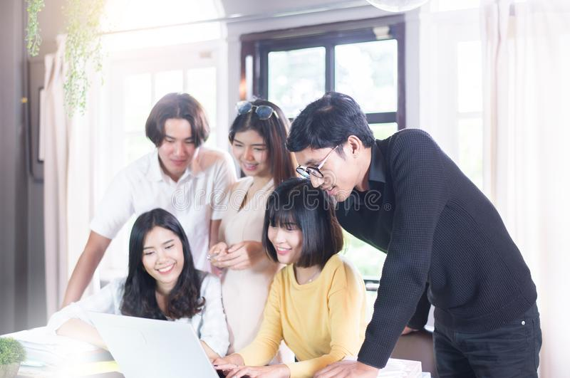 Grupo de sonrisa asiática joven y de usar el labtop y de escribir del Freelancer la nota en biblioteca de universidad fotos de archivo libres de regalías