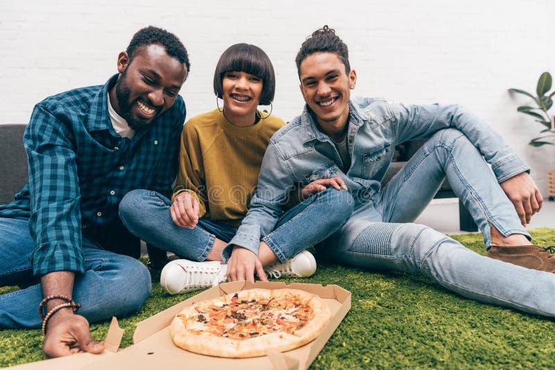grupo de sorriso de amigos multi-étnicos que comem a pizza e o assento imagens de stock royalty free