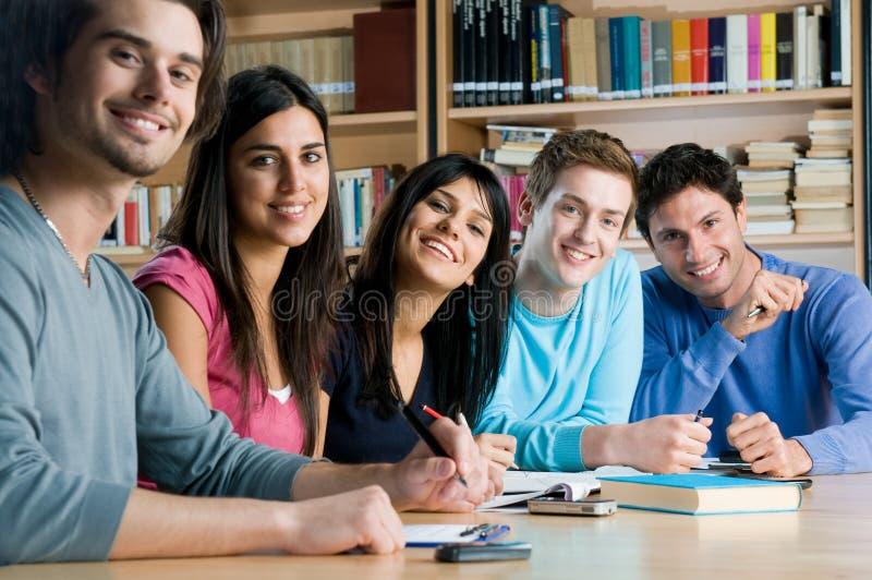 Grupo de sorriso de estudantes em uma biblioteca imagem de stock