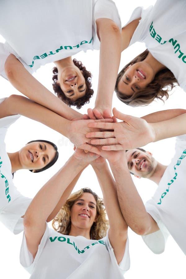 Grupo de sorriso de voluntários que empilham acima suas mãos imagens de stock