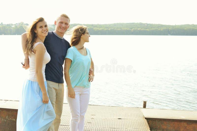 Grupo de sorriso dos amigos Férias de verão e conceito adolescente - meninas e menino perto do lago imagens de stock