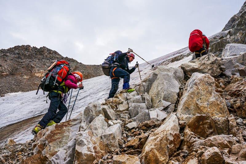 Grupo de subida de los escaladores a la montaña durante un alza que se divierte fotografía de archivo