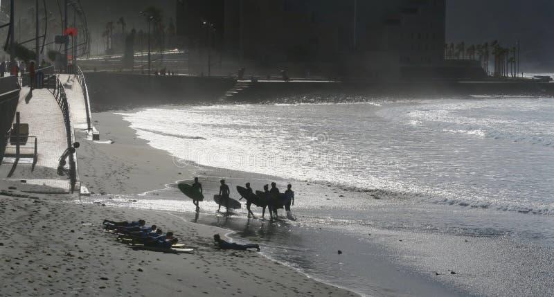Grupo de surfistas no sol de nivelamento na praia em Las Palmas de Gran Canaria imagem de stock royalty free