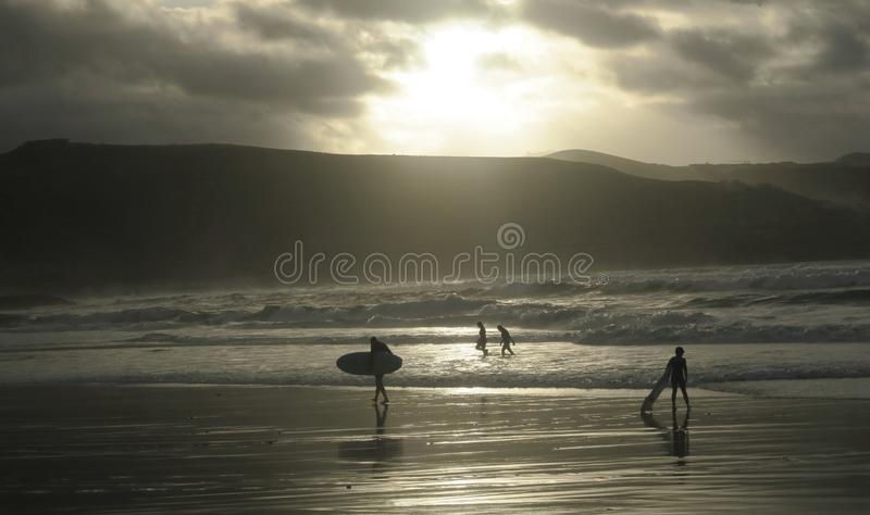 Grupo de surfistas no sol de nivelamento na praia em Las Palmas de Gran Canaria imagens de stock royalty free