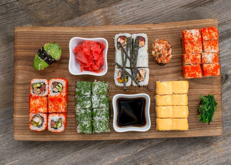 Grupo de sushi e de rolos com os hashis na tabela de madeira foto de stock
