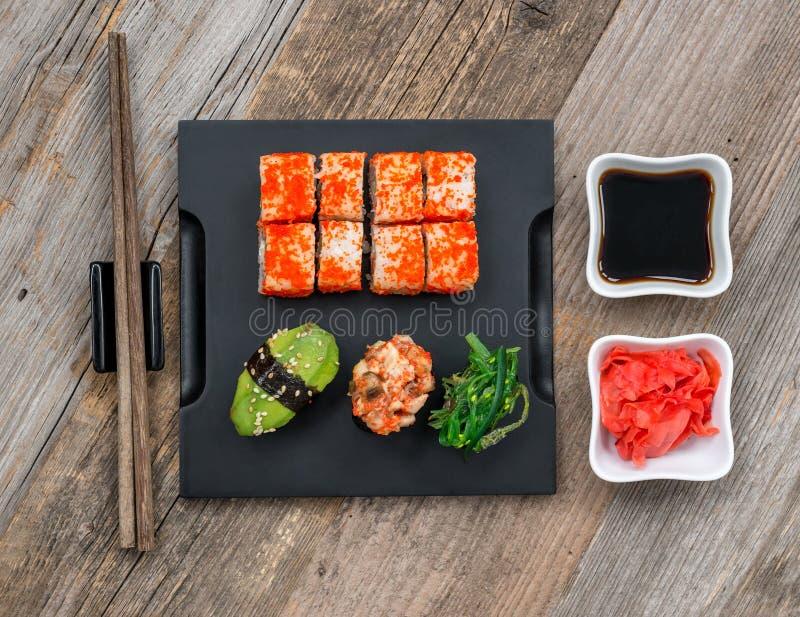Grupo de sushi e de rolos com os hashis na tabela de madeira fotos de stock