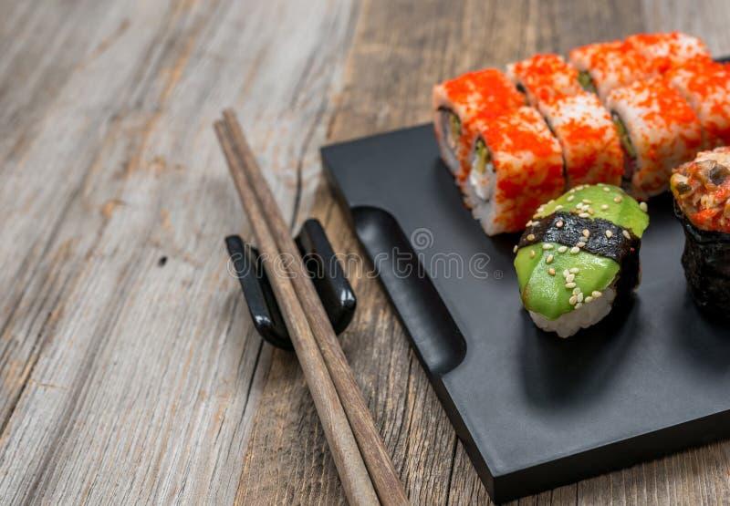 Grupo de sushi e de rolos com os hashis na tabela de madeira fotografia de stock