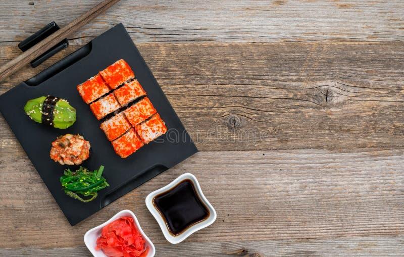 Grupo de sushi e de rolos com os hashis na tabela de madeira imagem de stock